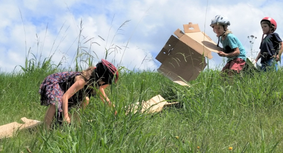 kids playng with cardboard boxes on a hill